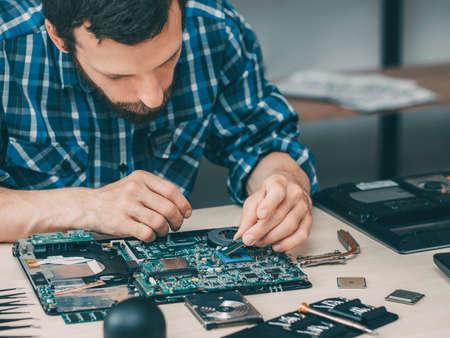 Foto de Computer technician workplace. Hardware repair upgrade. Man placing CPU on motherboard socket. Technology service. - Imagen libre de derechos