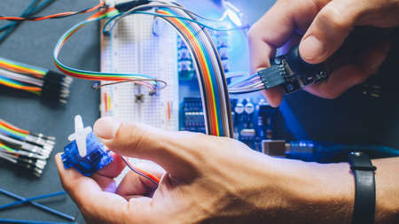 Photo pour Engineer inventing prototype. Robotic electronic module construction. Microcontroller programming. Hands working with electrical sensor. - image libre de droit