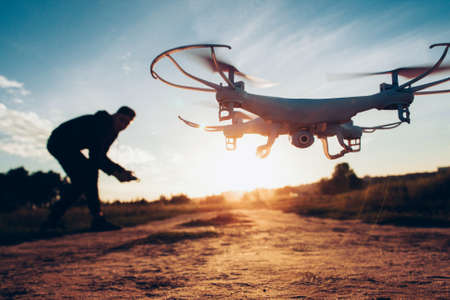 Foto de Drone trends and innovations. Modern hobby and leisure. Closeup of camera quadcopter controlled remotely by guy over blur sunset. - Imagen libre de derechos