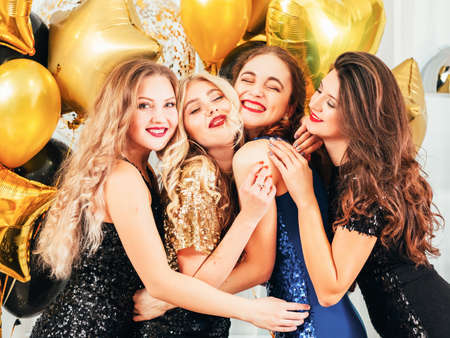 Photo for Fancy party. Festive occasion. Girls with evening makeup, in sparkling dresses posing over golden balloons, hugging each other. - Royalty Free Image