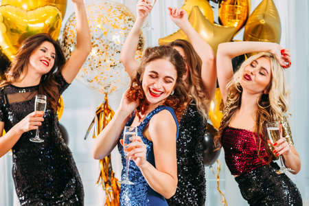 Photo for Fancy party. Ladies celebrating their college graduation at home. Girls dancing with champagne in room decorated with balloons. - Royalty Free Image