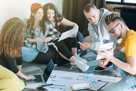 Photo for Millennial IT specialists studying business strategy. Young people cooperating in modern loft room, sitting on floor. - Royalty Free Image