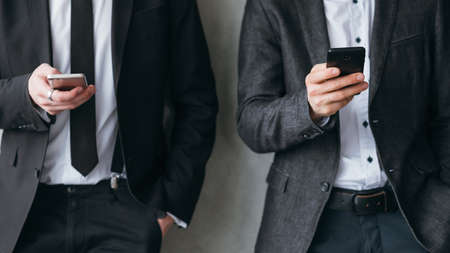 Photo for Social media addiction. Modern corporate life break time. Two men in business suits leaning on the wall, using smartphones. - Royalty Free Image