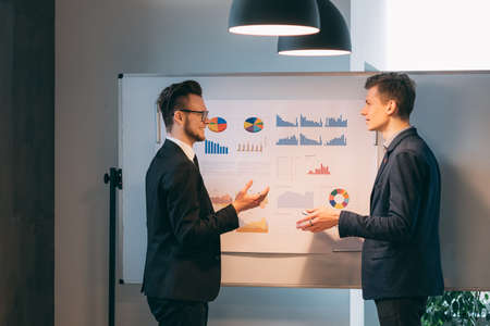 Photo for Corporate meeting. Two young men standing at the whiteboard with graphs, discussing startup business strategy. - Royalty Free Image