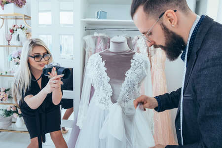 Photo pour Fashion boutique and store advertising. Clothing brand promotion service. Personal assistant and photographer presenting gowns. - image libre de droit
