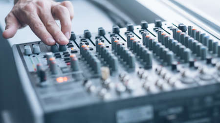 Photo for Professional sound console. Closeup of man hand mixing tracks, adjusting tune effects. - Royalty Free Image