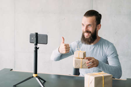 Photo for Sales management training. Hipster guy using smartphone on tripod to tell about tips for selling goods. Copy space. - Royalty Free Image