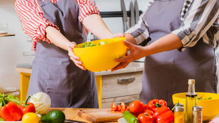 Foto per Vegetarian lifestyle. Cropped shot of women cooking together, holding yellow bowl with salad. - Immagine Royalty Free