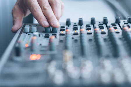 Photo for Sound recording studio. Closeup of man hand using professional audio mixer to adjust tune effects. - Royalty Free Image