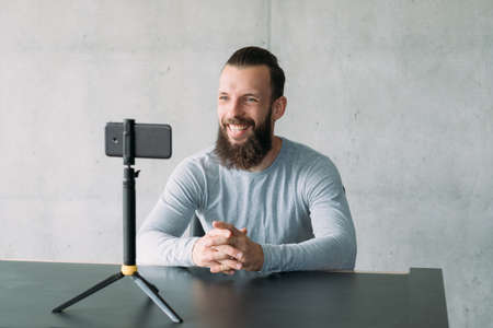 Photo for Modern business coaching. Confident hipster guy using smartphone camera to record speech video. Copy space. - Royalty Free Image