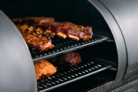 Photo pour Professional kitchen appliance. Poultry, beef and pork meat, ribs cooked in BBQ smoker. - image libre de droit