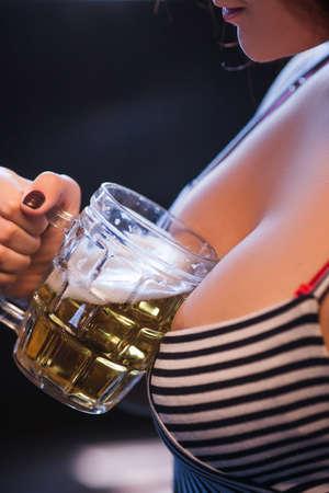 Foto de Woman with big breasts holding a glass of beer. Every mans dream girlfriend concept - Imagen libre de derechos