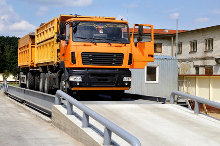 Photo pour orange truck with grain is weighed on the scales in the grain storage area. Truck scales - image libre de droit