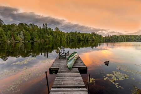 Photo pour Green Canoe and Chairs on a Dock Next to a Lake at Sunset - Haliburton Highlands, Ontario, Canada - image libre de droit
