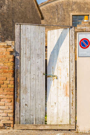 Photo for temporary door of old wooden boards with deadbolt but smashed and held together by a garter - Royalty Free Image
