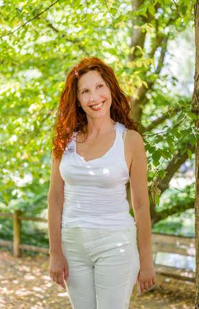 Foto de happy woman in menopause standing and smiling in a garden, joyfully living the change of life - Imagen libre de derechos