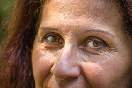 Photo for close up of eyes of mature woman with reddish brown hair, wrinkles and crow feet and with slight Strabismus of Venus - Royalty Free Image