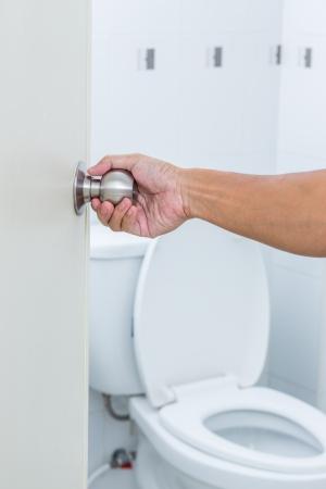 Foto de Man hand open toilet door - Imagen libre de derechos