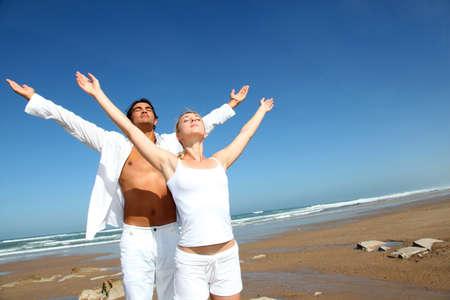 Photo pour Couple doing yoga exercises on the beach - image libre de droit