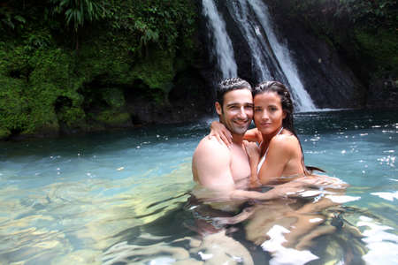 Photo for Happy couple bathing near waterfall in island - Royalty Free Image