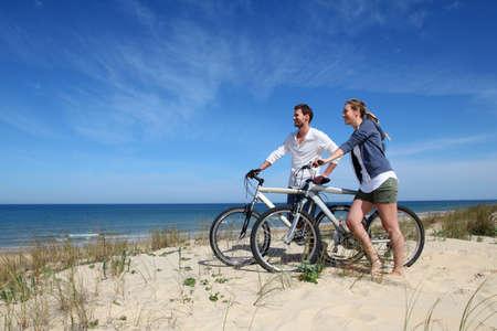 Photo pour Couple standing on a sand dune with bicycles - image libre de droit