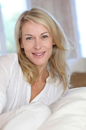 Photo for Portrait of blond mature woman relaxing in sofa - Royalty Free Image