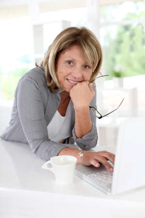 Photo pour Senior woman in front of laptop with cup of coffee - image libre de droit