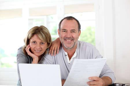 Photo pour Senior couple at home declaring income on internet - image libre de droit