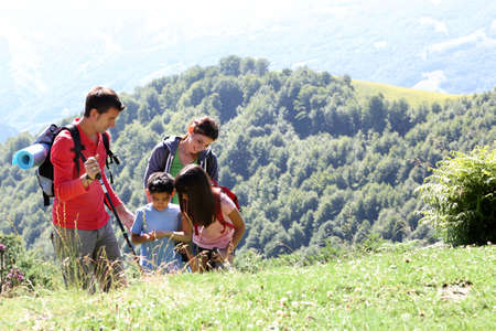 Photo pour Family on a trekking day looking at wild flowers - image libre de droit
