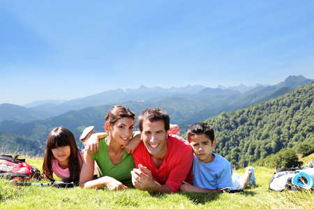 Photo pour Portrait of happy family laying on the grass in mountain - image libre de droit