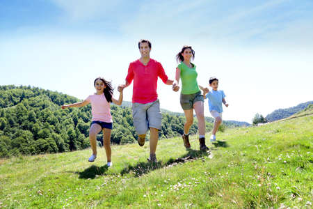 Foto de Happy family enjoying and running together in the mountains - Imagen libre de derechos