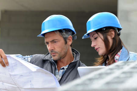 Photo pour Closeup of engineers reading plan on building site - image libre de droit