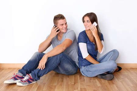 Photo pour Young couple talking on mobile phone - image libre de droit