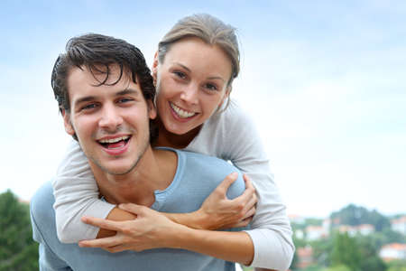 Photo for Man giving piggyback ride to girlfriend outside - Royalty Free Image