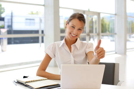 Cheerful office-worker showing thumbs up in front of laptop