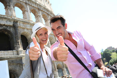 Photo pour Couple showing thumbs up in front of the Coliseum - image libre de droit