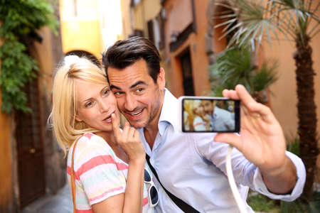 Photo pour Couple of tourists taking picture in the streets of Rome - image libre de droit