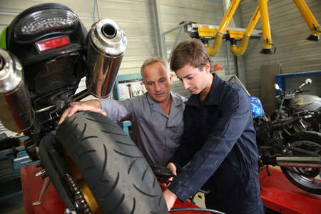 Teacher with students in mechanics working on bike