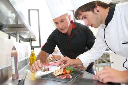 Foto de Chef helping student in catering to prepare foie gras dish - Imagen libre de derechos