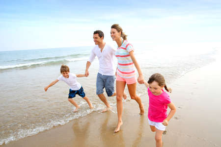 Photo pour Happy family running on the beach - image libre de droit