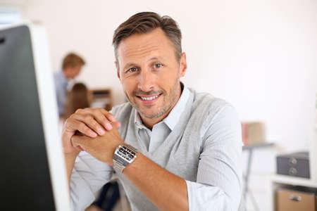 Foto de Cheerful man sitting in office and working on desktop - Imagen libre de derechos