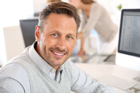 Photo pour Cheerful man sitting in office and working on desktop - image libre de droit