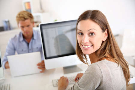 Photo for Portrait of smiling office worker in front of desktop - Royalty Free Image