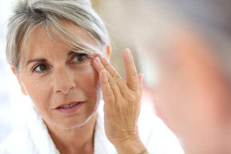 Photo pour Senior woman applying anti-wrinkles cream  - image libre de droit