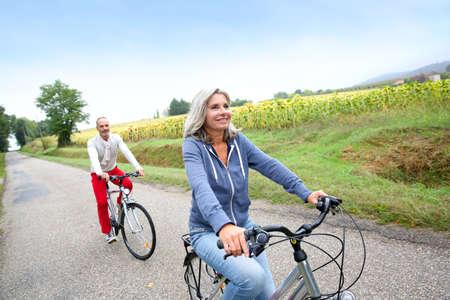 Photo pour Senior couple riding bicycle in countryside - image libre de droit