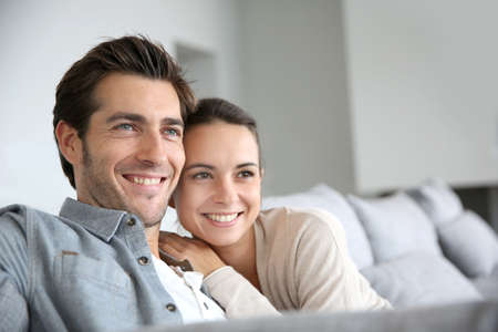 Photo pour Couple at home relaxing in sofa - image libre de droit