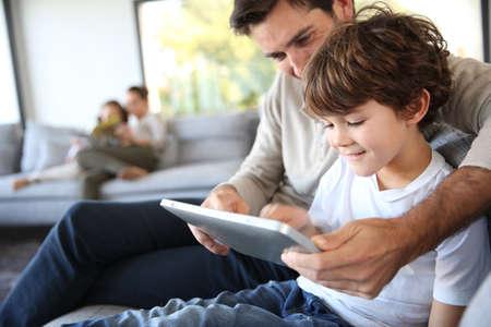 Foto de Father and son playing with digital tablet - Imagen libre de derechos