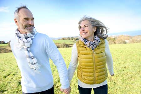 Foto de Cheerful senior couple running in countryside - Imagen libre de derechos