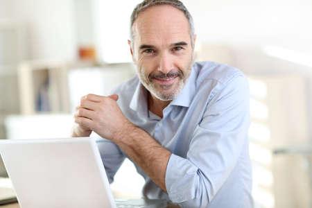 Photo pour Senior businessman working on laptop computer - image libre de droit