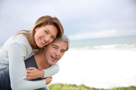 Photo pour Mature handsome man carrying woman on his back - image libre de droit